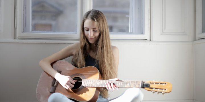 アコースティックギターを練習する女性